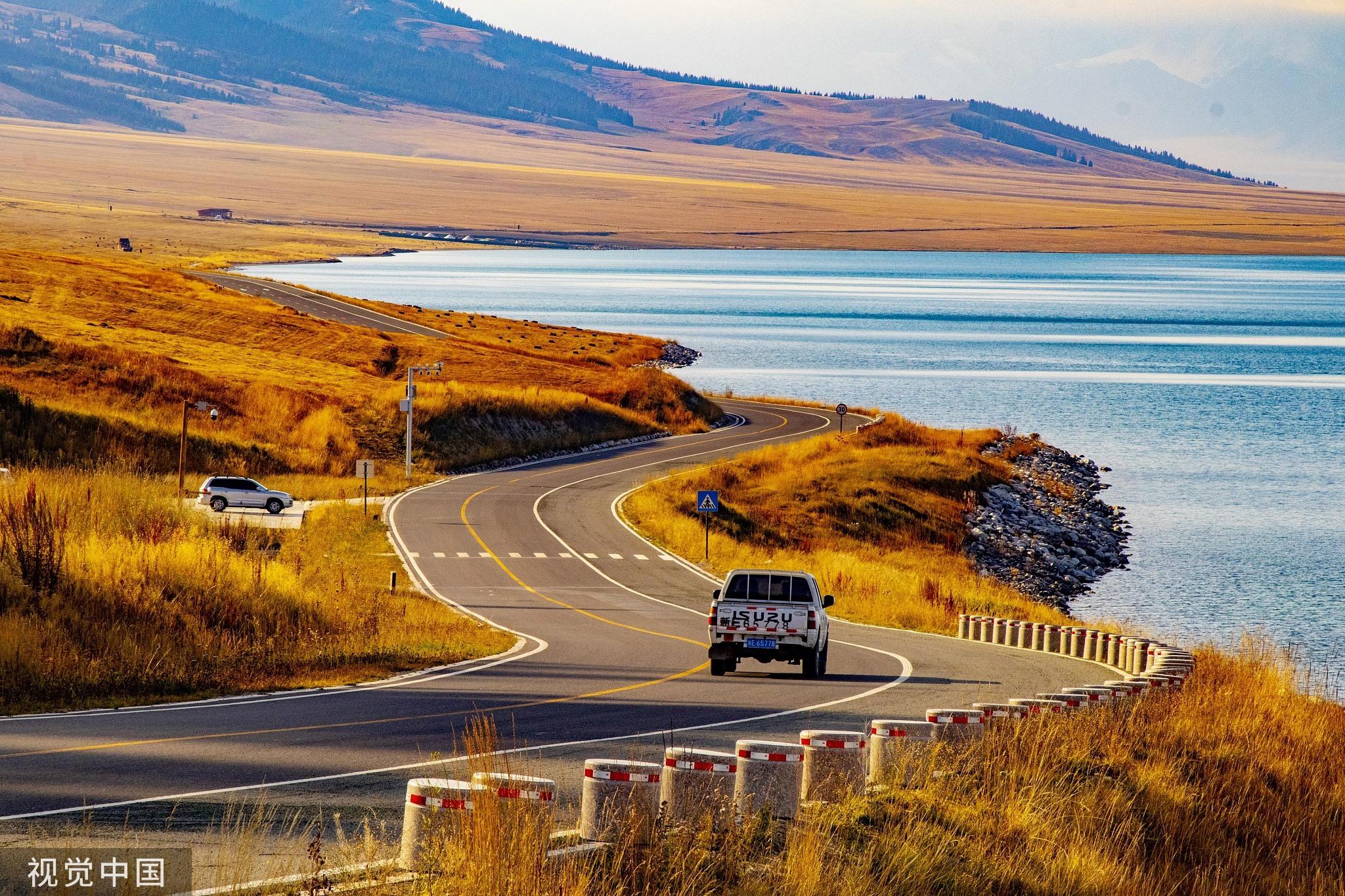 金秋九月的赛里木湖畔,泛黄的草地上点缀着毡房,山巅松林叠嶂、山下湖水湛蓝,湖面映衬出辽阔的天空。蔡增乐/视觉中国