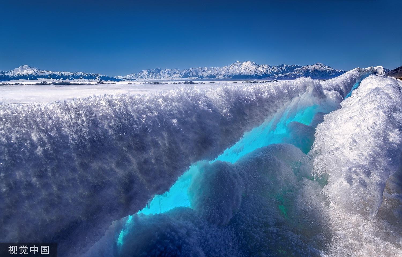 到了冬天,赛里木湖千里冰封,厚厚的蓝色冰层随处可见,阳光突破云层的遮挡照射下来,湖面变得晶莹剔透。